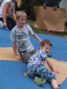 At the local food festival in the park, slope + tarpaulin + scrap cardboard = great fun