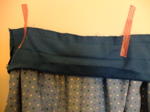 Waistband, folds pressed in, attached to skirt