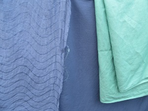 The once white now blue fabric hanging on the line with some not quite so in your face any more green linen