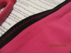 Contrast zig zag on the Fold OVer Elastic (FOE), deliberate design feature, not laziness in changing thread
